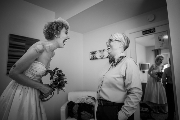 Lesbian bride laughs with matron of honor before Chicago gay wedding